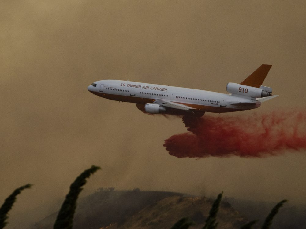 Tanker 910 works a fire in Live Oak Canyon near Banning in heavy winds